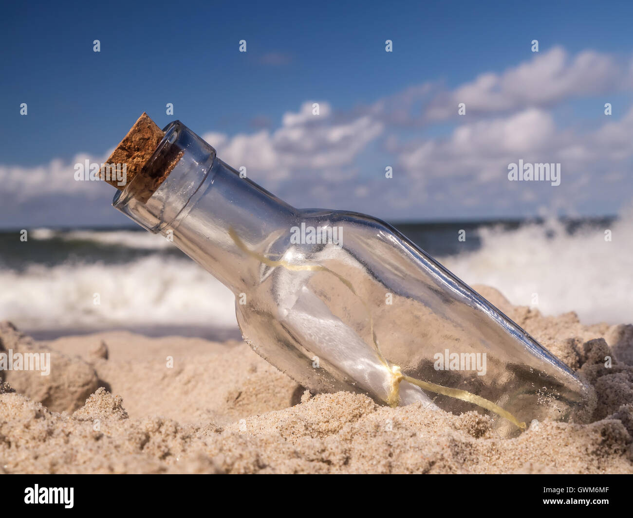 Corked bottle with message stuck in the sand on the beach - Stock Image