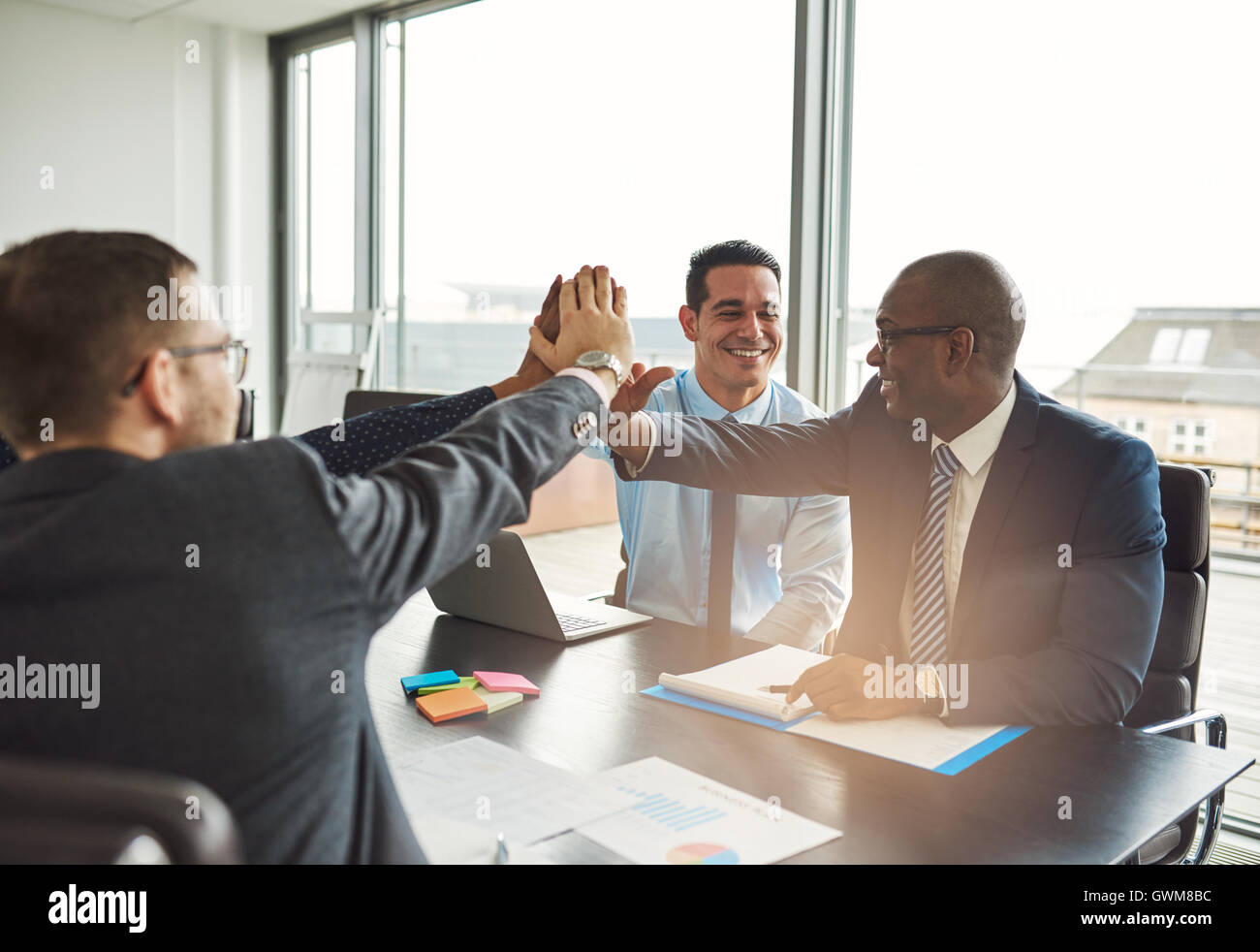 Successful multiethnic business team congratulating each other on an achievement giving a high fives gesture with - Stock Image