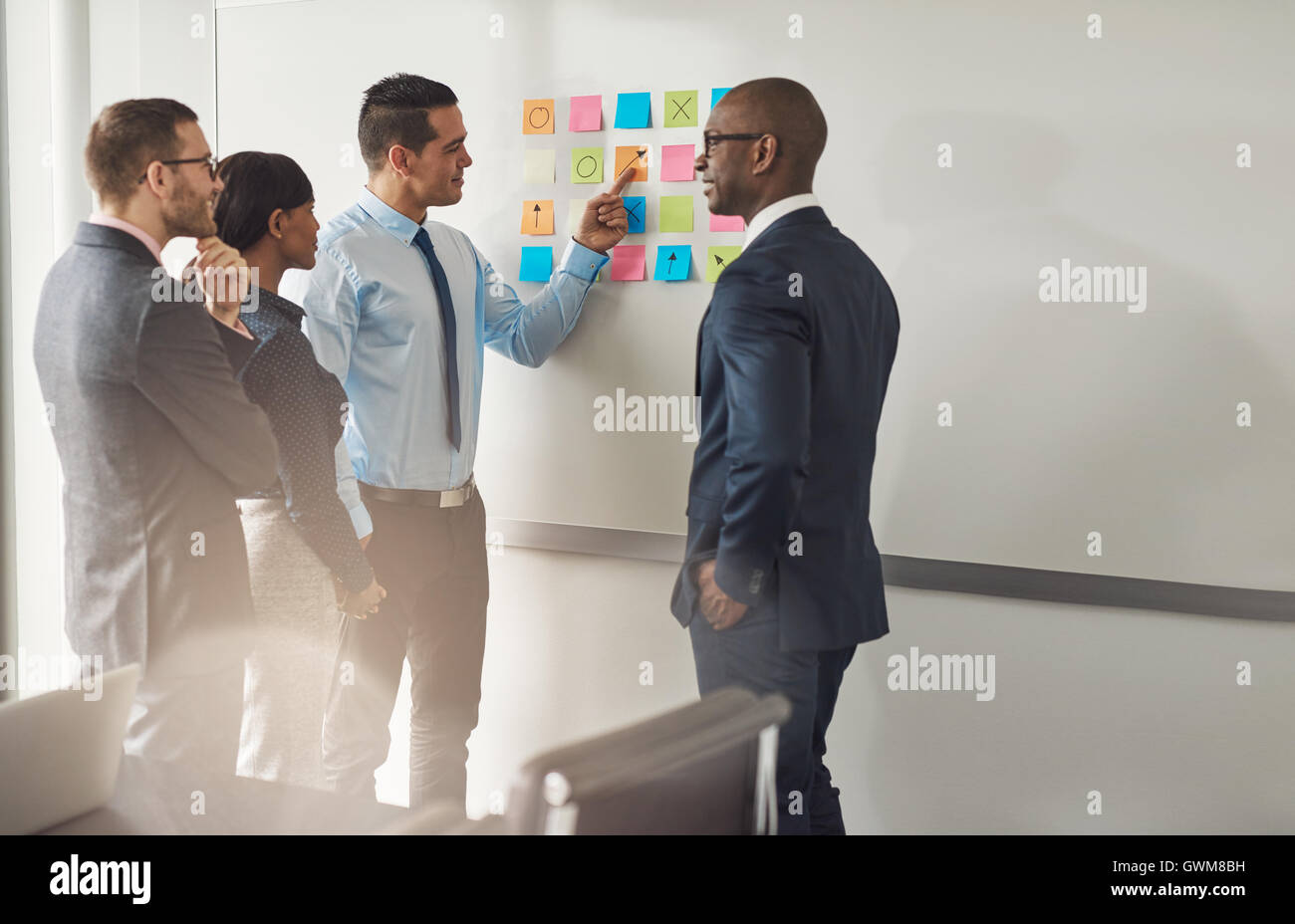 Group of multiracial businesspeople standing chatting as they point to a set of colorful memos on the wall trying - Stock Image