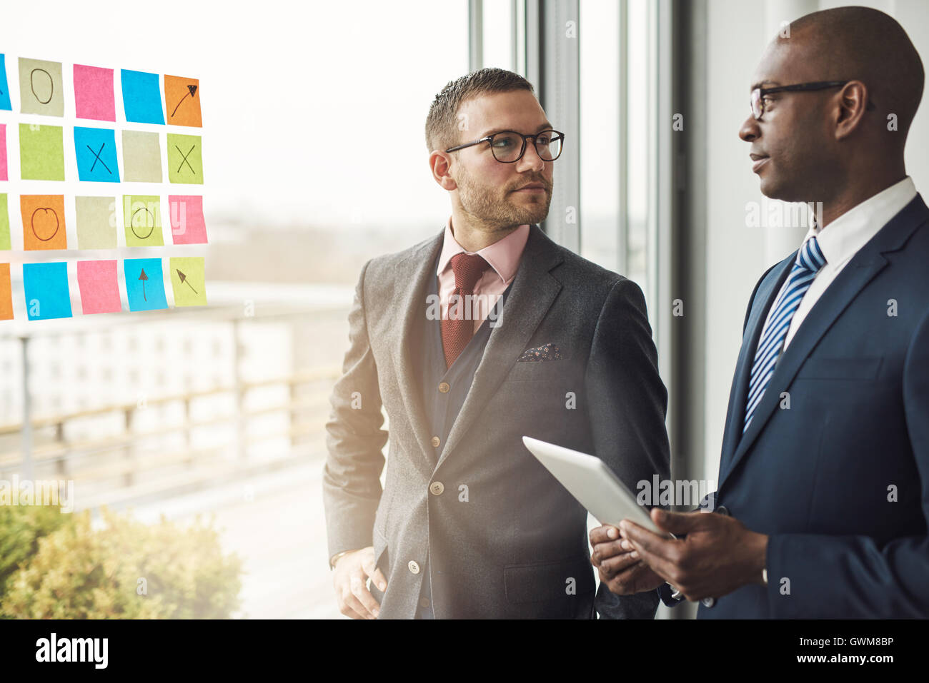 Caucasian and African businessman in a meeting standing in front of colorful memos on the glass of a window in the - Stock Image