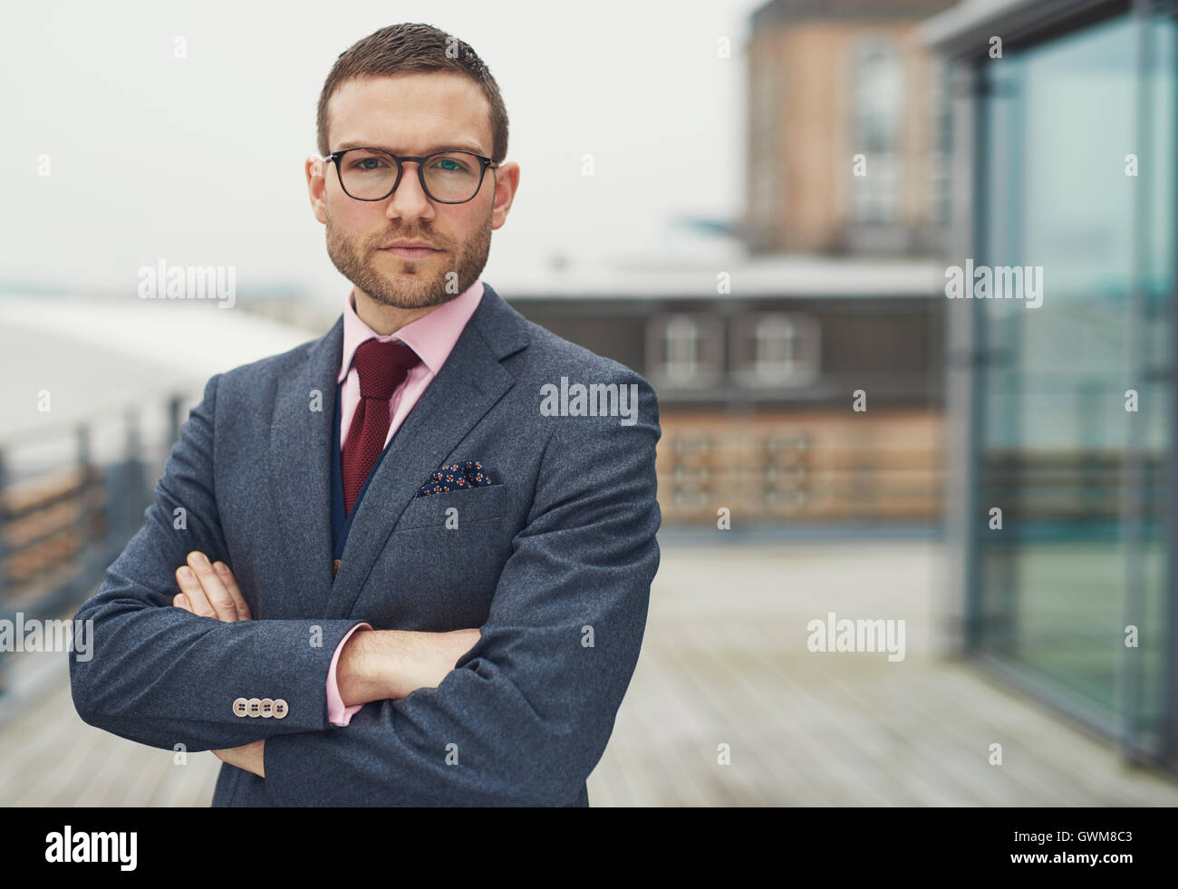 Confident stylish businessman wearing glasses standing on an open-air balcony looking thoughtfully at the camera - Stock Image