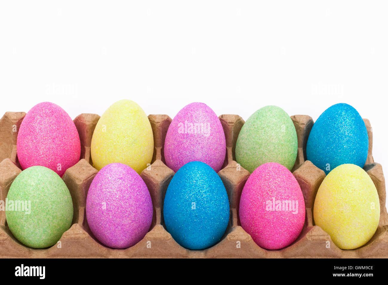 Glitter covered fake Easter eggs in an egg carton - Stock Image
