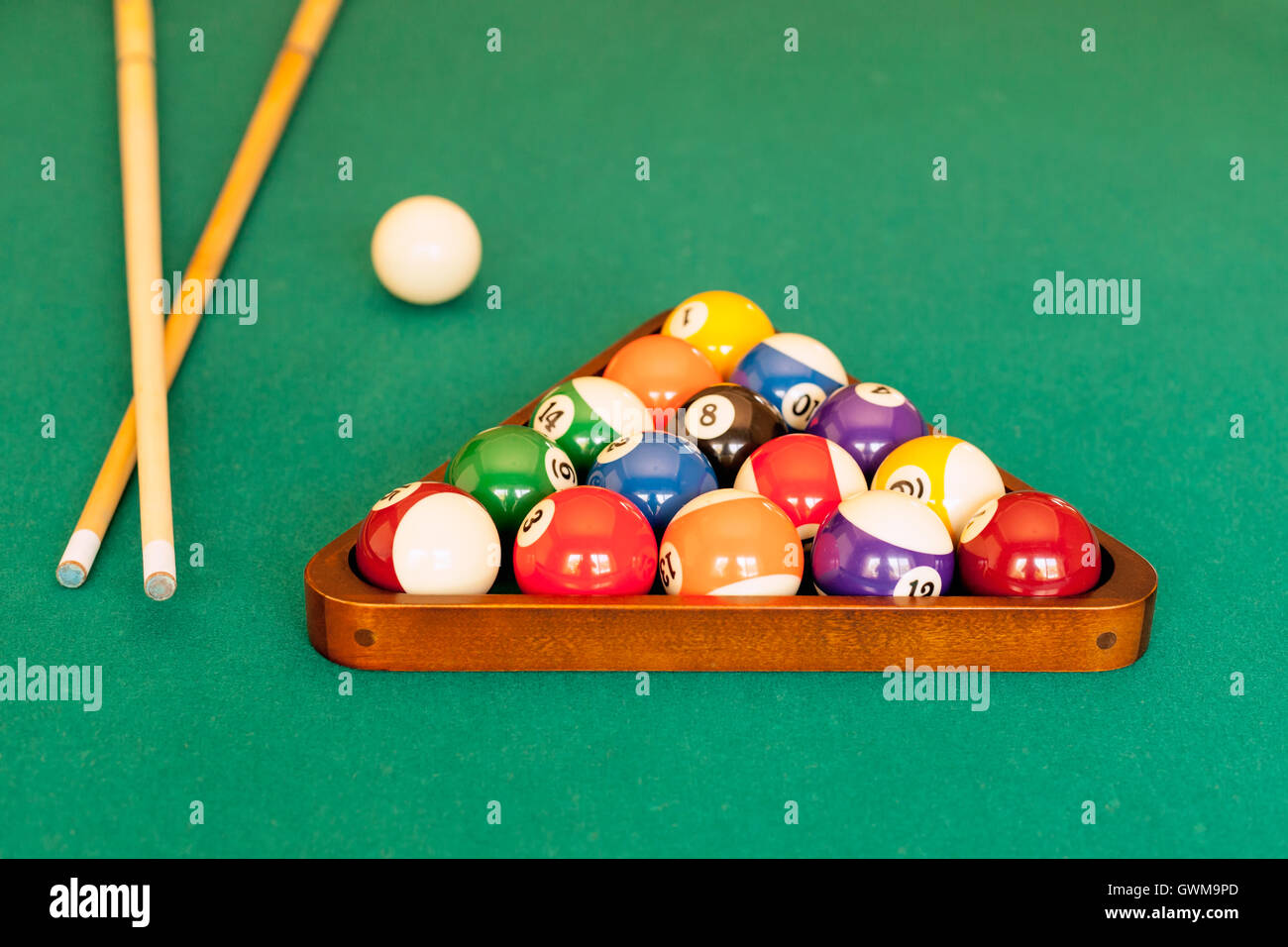 Pool cue sticks, a cue ball and a rack of balls ready for a game of eight-ball pool. Stock Photo