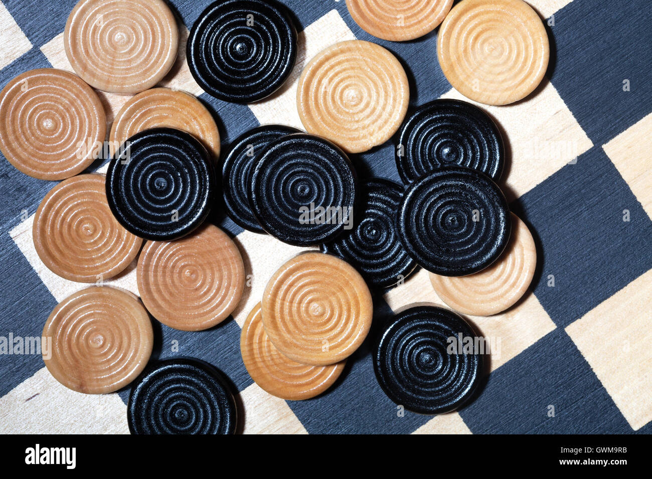 Checkers or draughts on a checker board Stock Photo