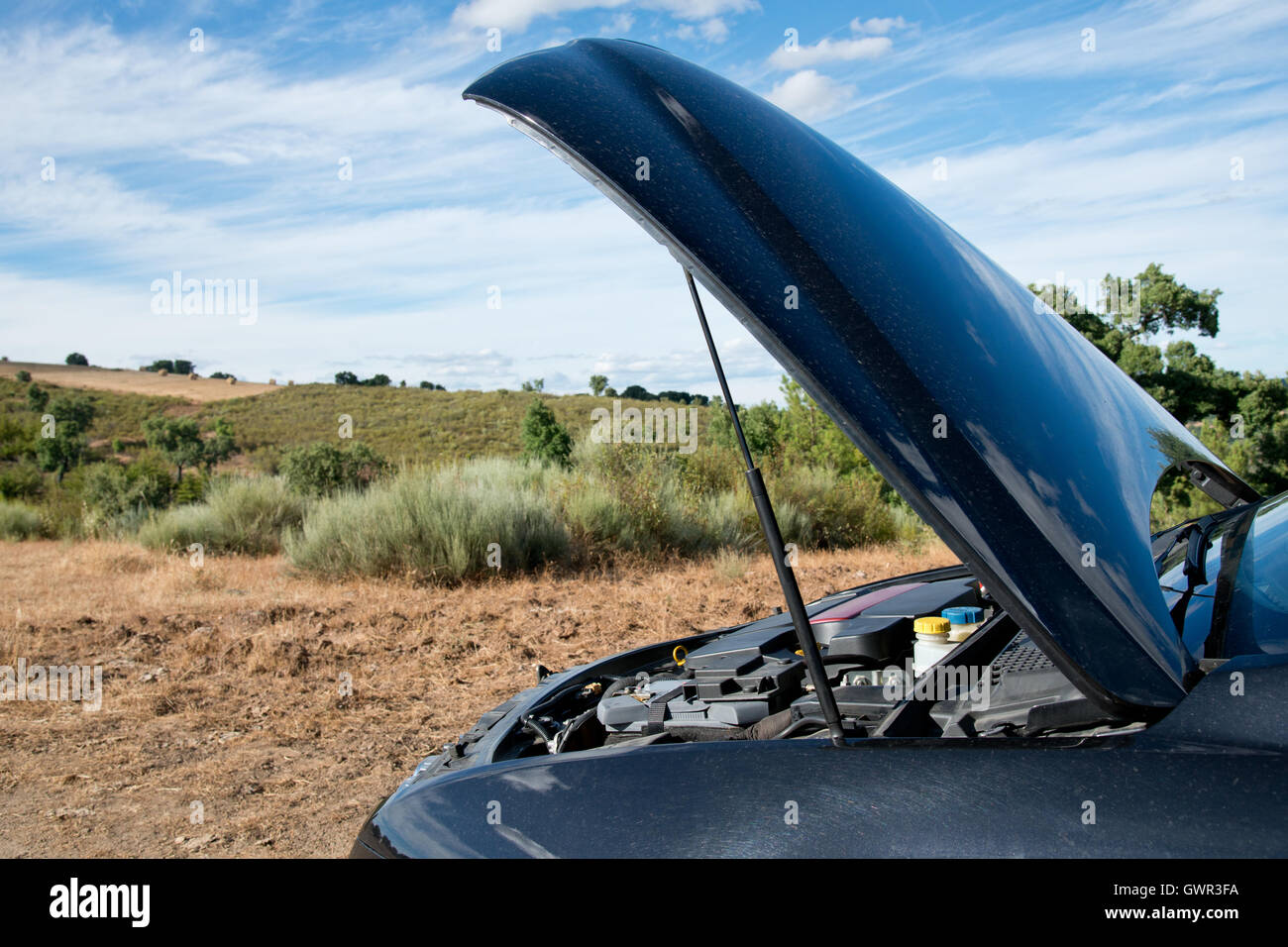 Close up of a broken down car, engine open, in a rural area - Stock Image