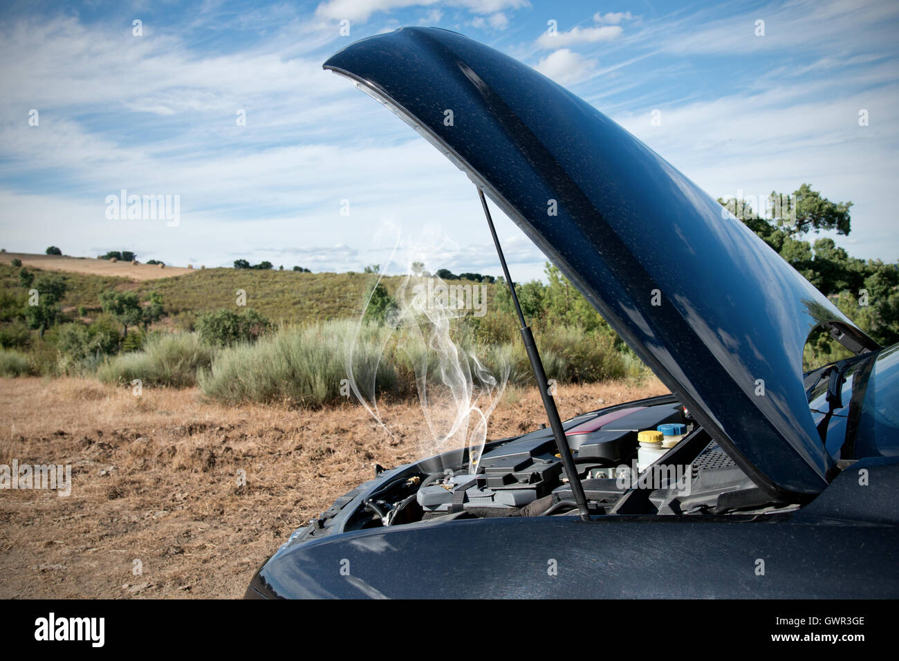 Close up of a broken down car, engine open with smoke, in a rural area - Stock Image