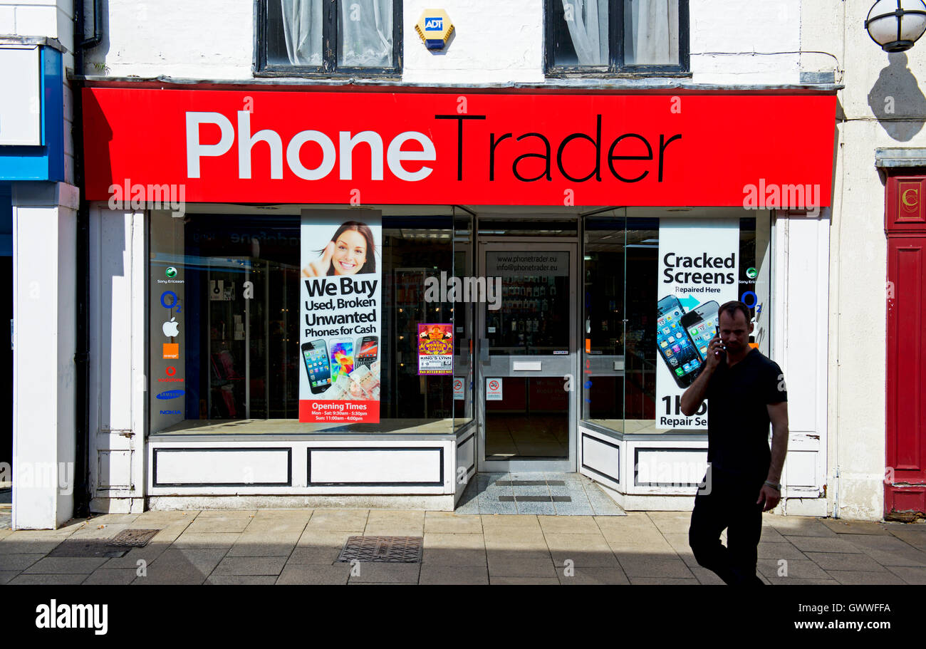 Man walking past Phone Trader shop, England UK - Stock Image