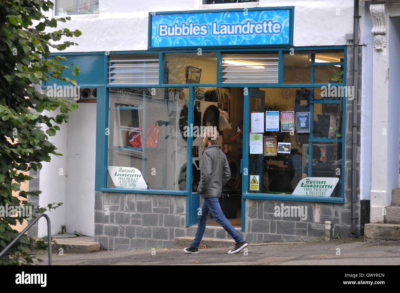 Student walking past a laundrette in Falmouth, Cornwall - Stock Image