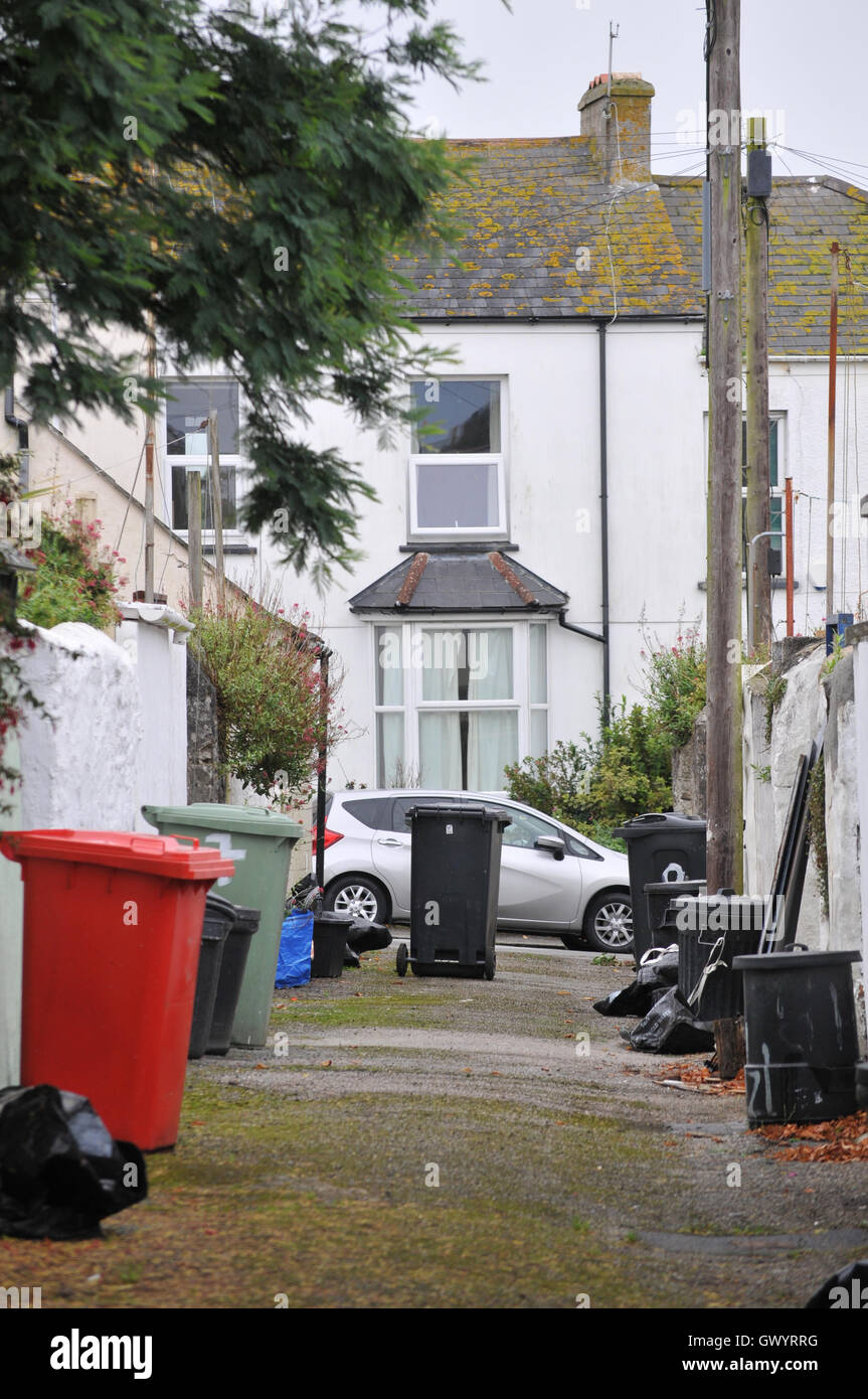 Road behind houses in Falmouth, Cornwall with rubbish bins - Stock Image