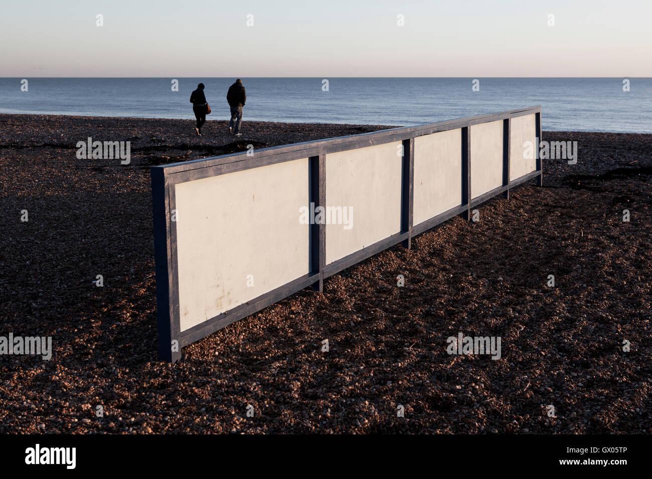 People walking along the seashore. Color photograph. - Stock Image