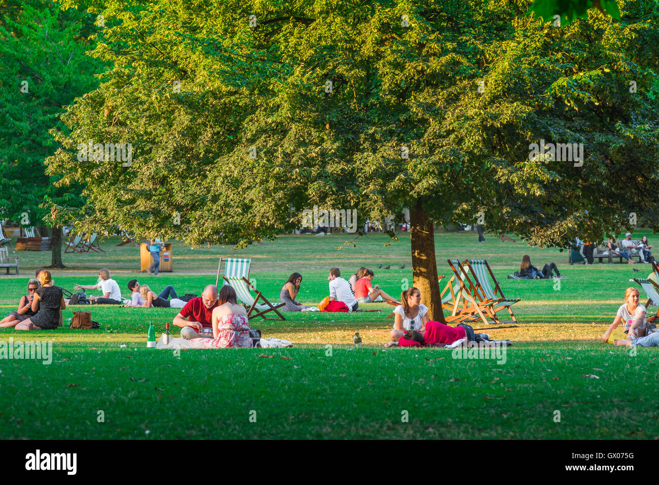 London park summer, in St James's Park, London, couples dine,relax and socialise in the light cast by the setting - Stock Image