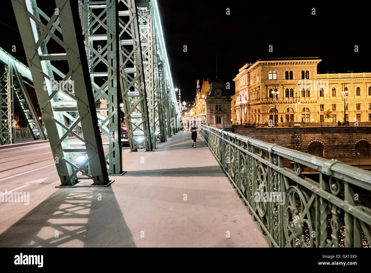 young woman runner running on city bridge road budapest liberty bridge night - Stock Image