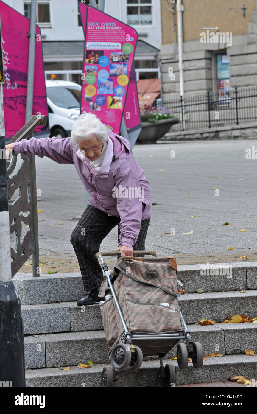 An old lady pulls her shopping trolley up some steps in Falmouth, Cornwall - Stock Image