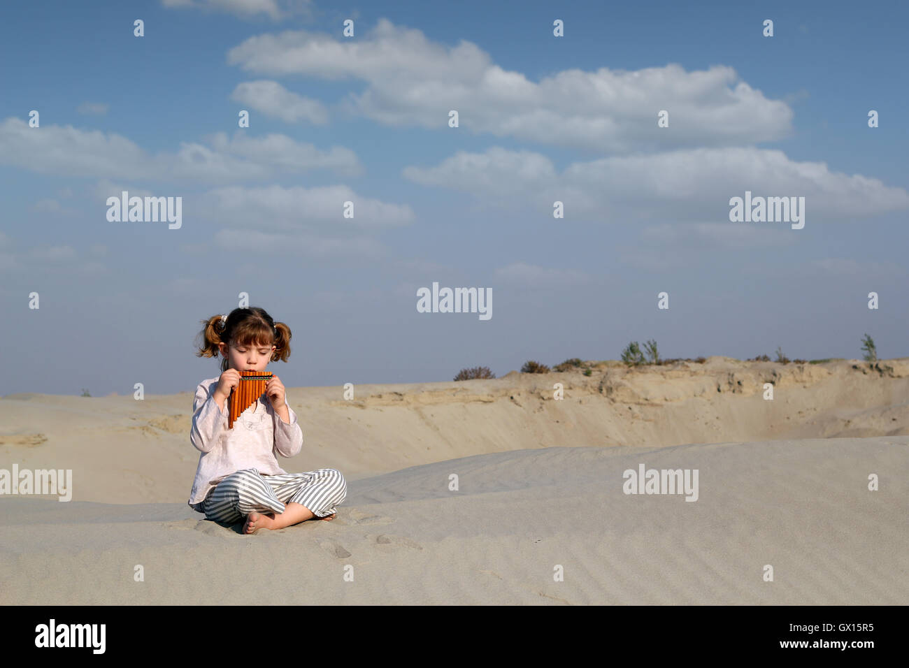 little girl play music on pan pipe - Stock Image