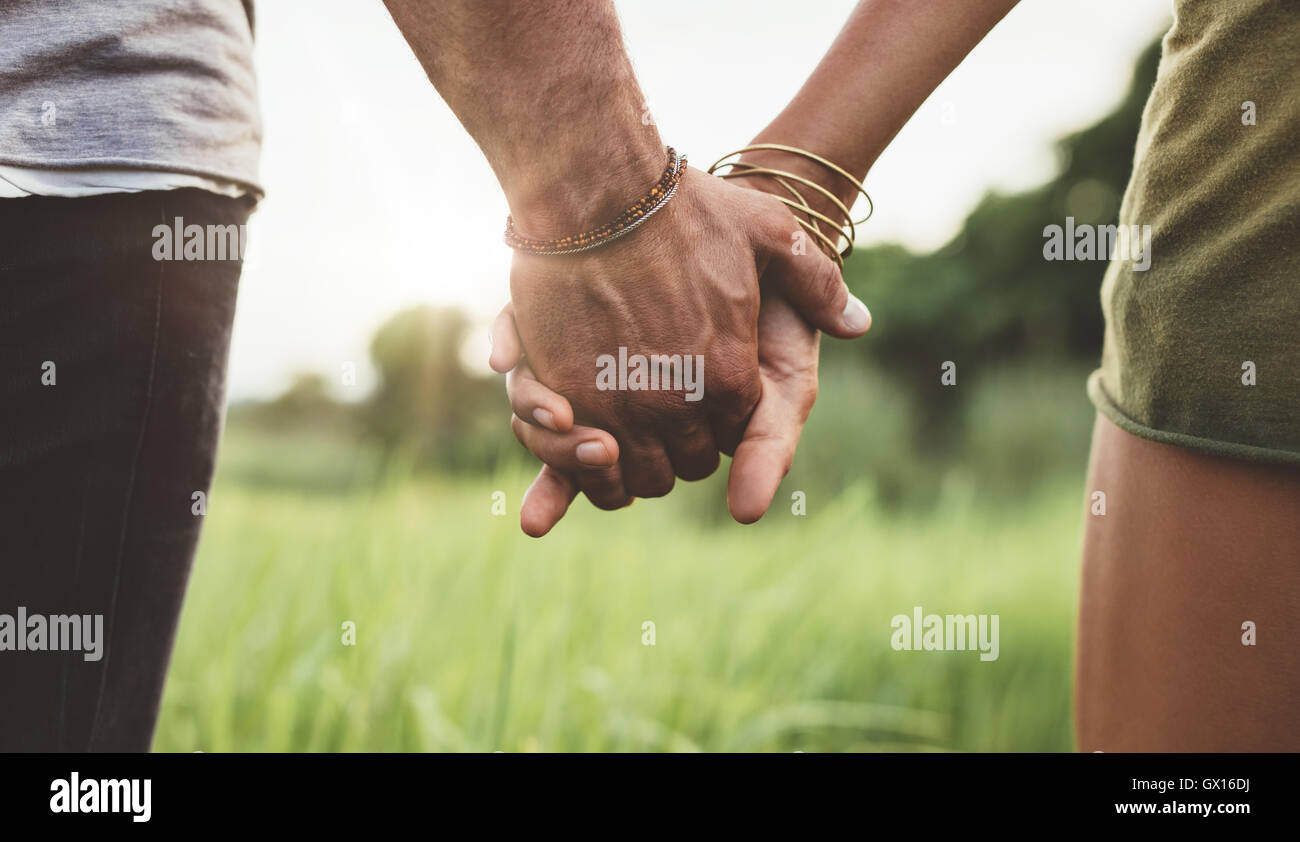 Young couple walking through meadow hand in hand. Close up shot with focus on hands of man and woman. - Stock Image