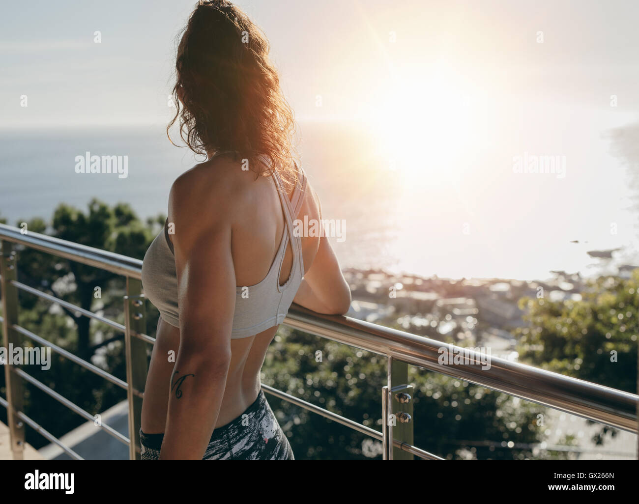 Rear view shot of woman standing by a railing in balcony and looking away on a bright sunny day. - Stock Image