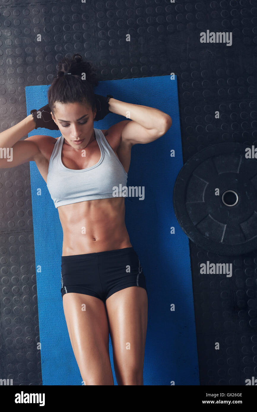 Top view of muscular young woman doing sit ups on an exercise mat. Fitness female lying on yoga mat with her hands - Stock Image