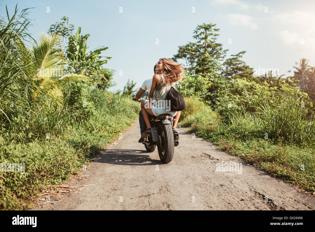 Rear view of young couple riding motorcycle on rural road. Woman with her boyfriend riding on motorbike on a summer - Stock Image