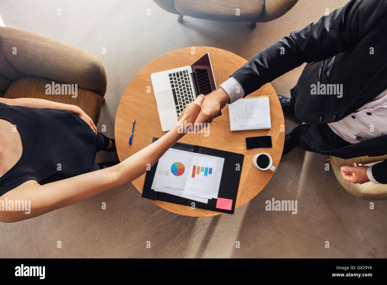 Top view of young business partners shaking hands over deal at office. Focus on handshake. - Stock Image