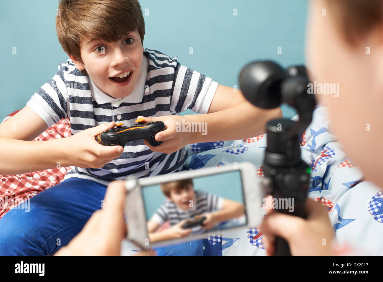 Two Boys Recording Gaming Blog In Bedroom - Stock Image