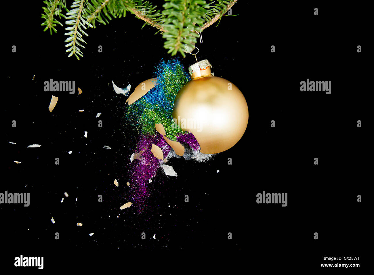 Christmas ball exploding. Colored glitters falling. - Stock Image
