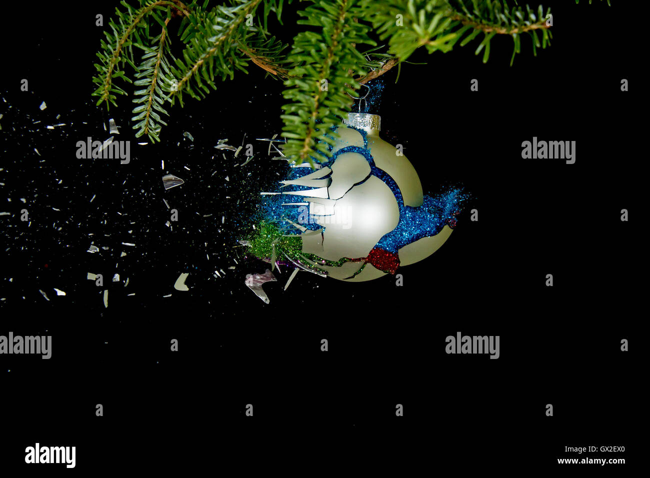 Christmas ball exploding. Glitters falling down. - Stock Image