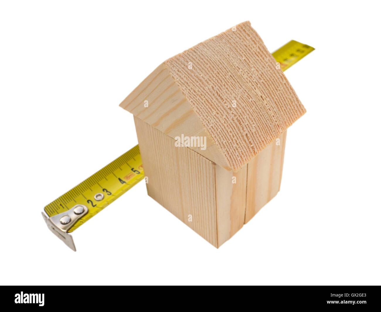 House of wooden building blocks with yellow ruler isolated on white - Stock Image