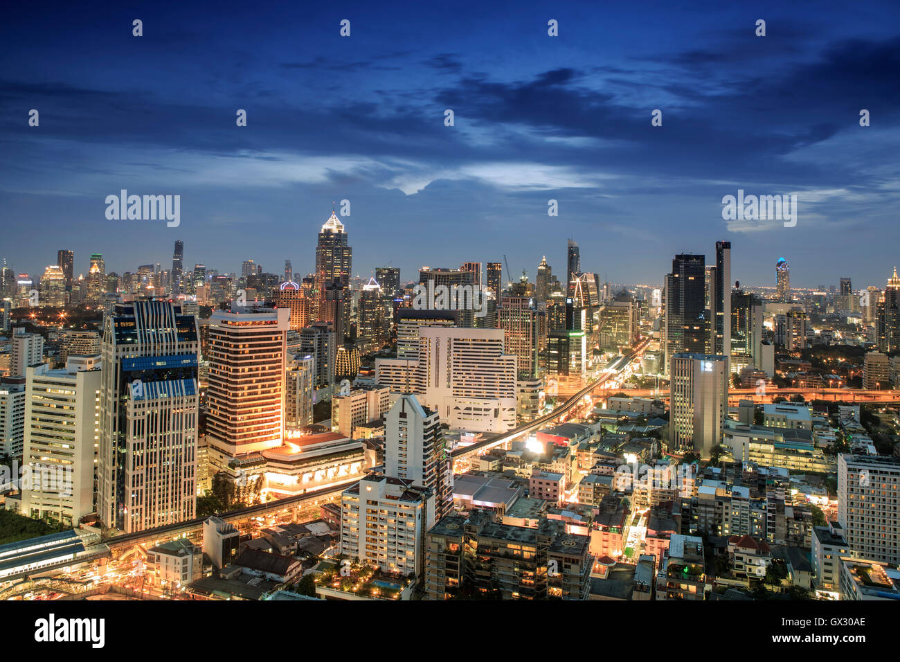 Bangkok city skyline at night - Skytrain train line & main tourist area around Sukhumvit showing Chit Lom and - Stock Image