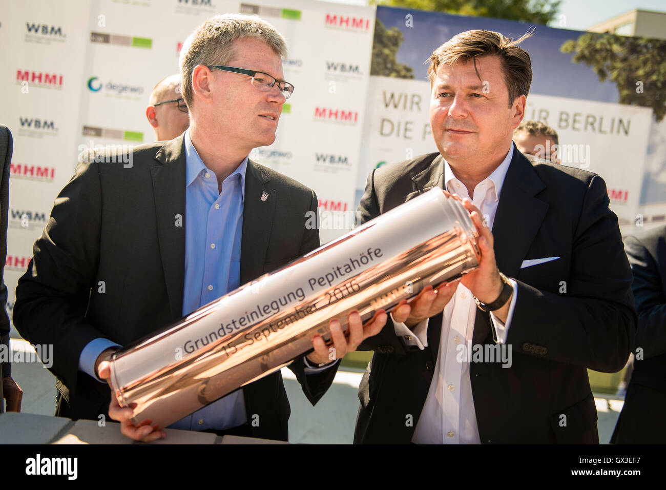 """The borough mayor of Berlin-Spandau, Helmut Kleebank (SPD, l-r), and the senator for city development and environment, Andreas Geisel (SPD), fill a time capsule with building plans and a daily newspaper, at the laying of the first stone for the residential construction project """"Pepitahoefe"""" in Berlin, Germany, 15 September 2016. The Pepitahoefe are a new construction project by degewo and the Wohnungsbaugesellschaft Berlin-Mitte GmbH. A total of 1024 apartments are to be built on the 58,700 square metre site by the end of 2018. PHOTO: GREGOR FISCHER/DPA Stock Photo"""