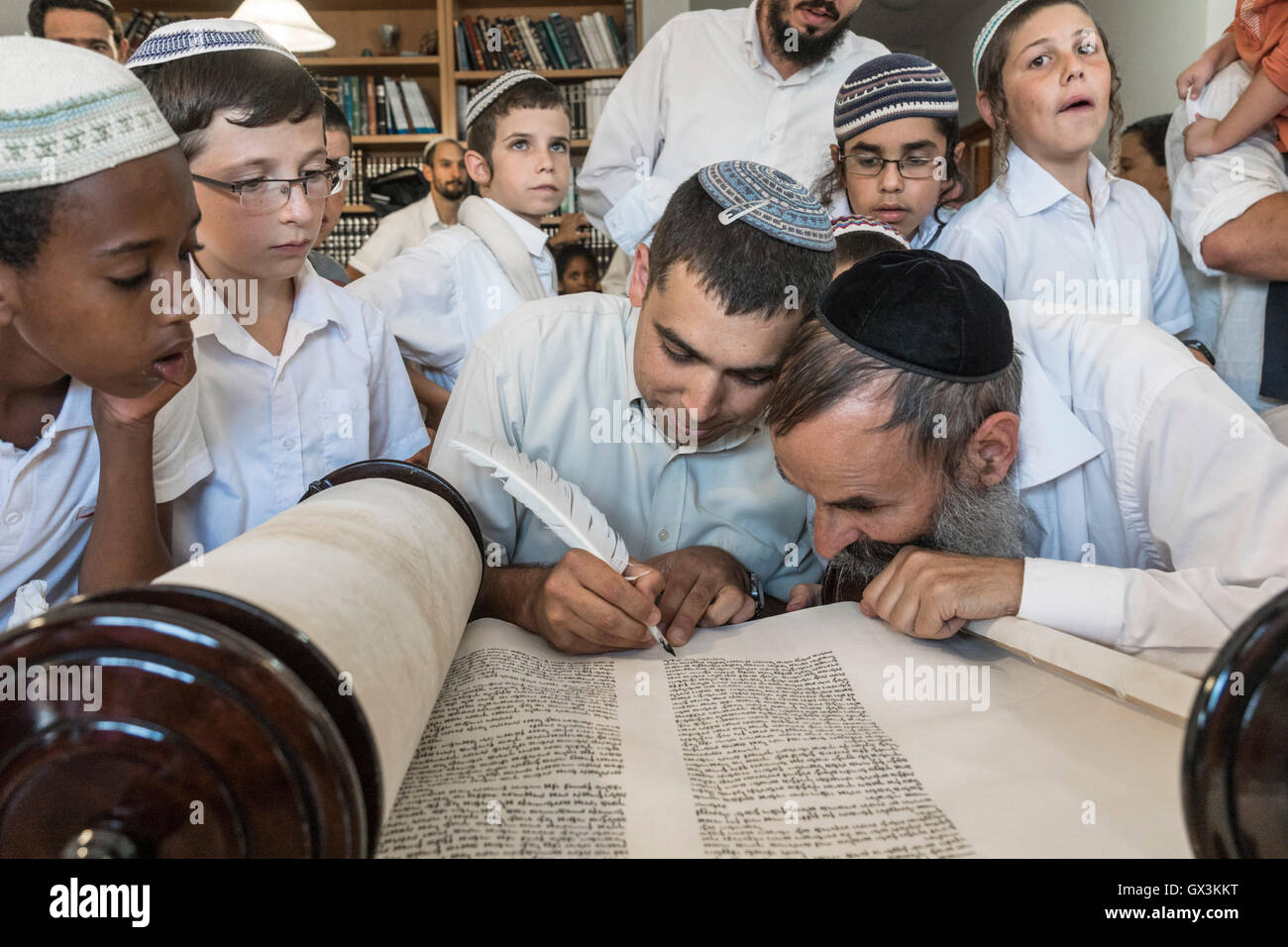 Neria, Israel. 15th September, 2016. A group of childern overlook a scrivener writing the last letters in the holy - Stock Image