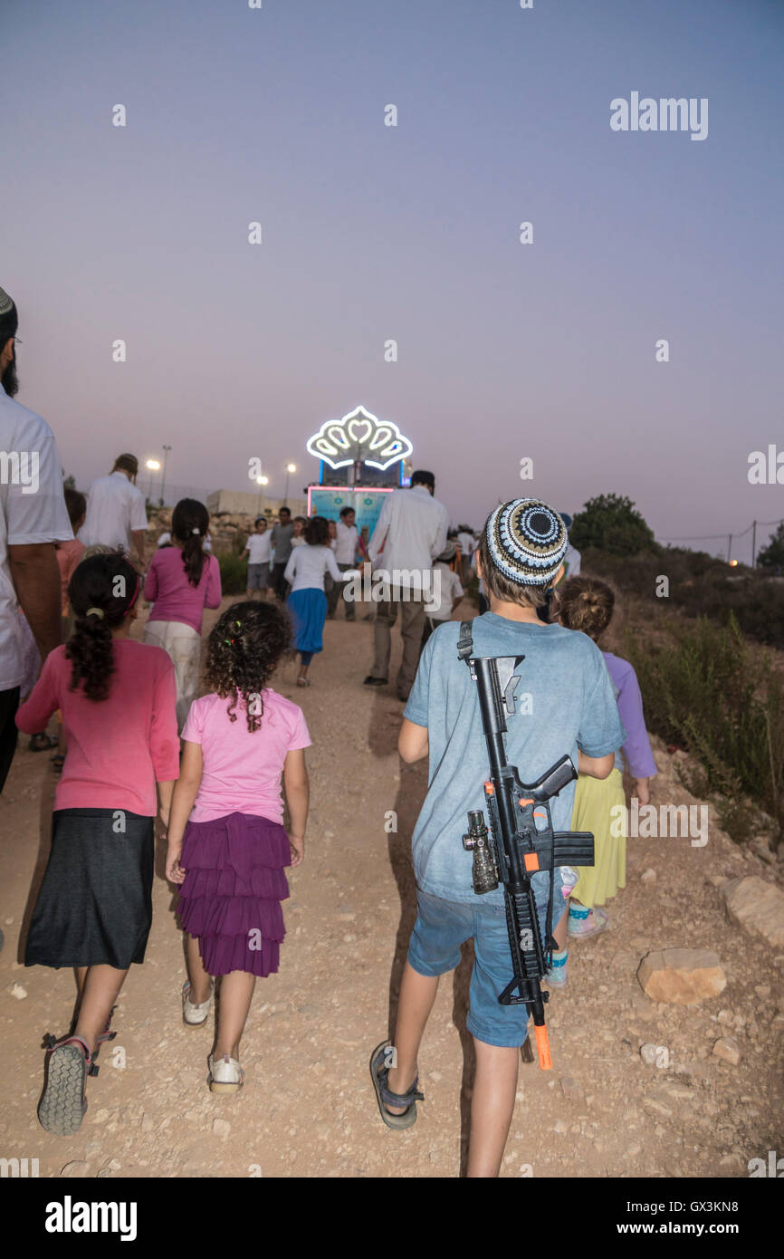 Neria, Israel. 15th September, 2016. Neria, Israel/West Bank. A boy with a toy rifle walks toward a truck with a - Stock Image