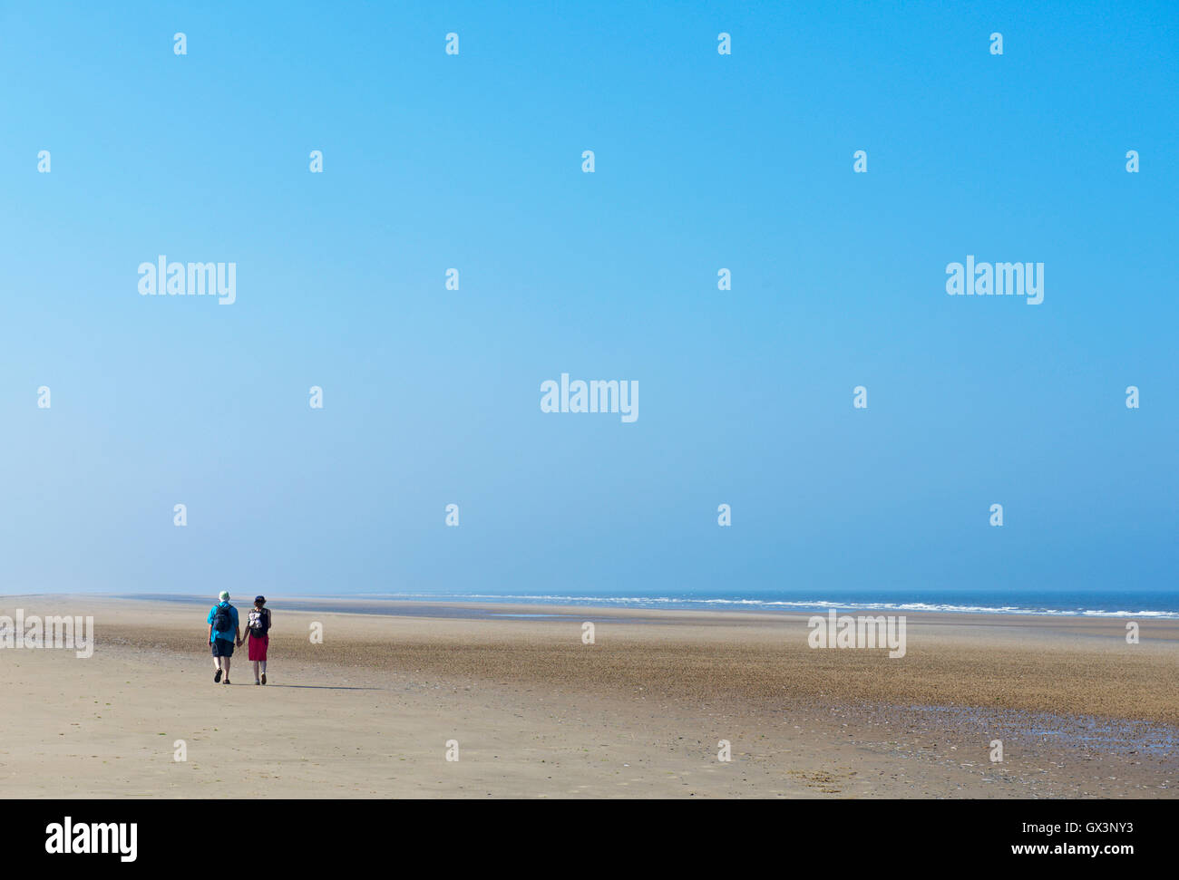 Couple walking along a deserted beach at Titchwell, North Norfolk, England UK - Stock Image