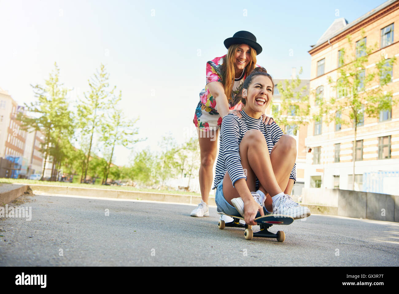 a705f5a7 Happy young woman in tie dye clothing and black hat pushing friend on  skateboard on road