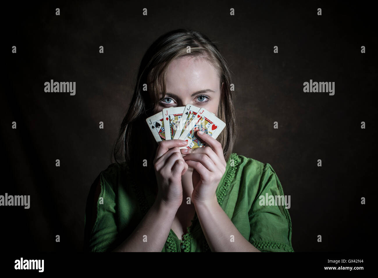 Woman hiding face with playing cards - Stock Image