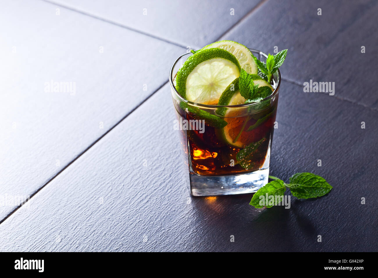 Drink with cola, lime , ice  and peppermint leaves - Stock Image