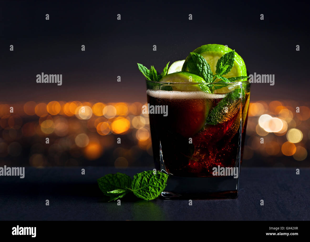 Cola with lime , ice  and peppermint on a background of night city - Stock Image