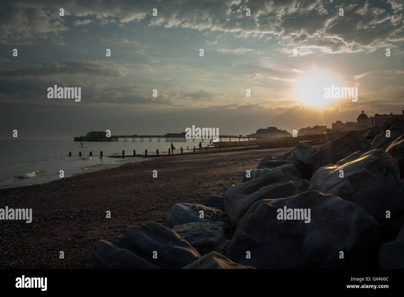 A beautiful sunset over the beach, sea and Worthing Pier in Worthing, West Sussex, England. Stock Photo