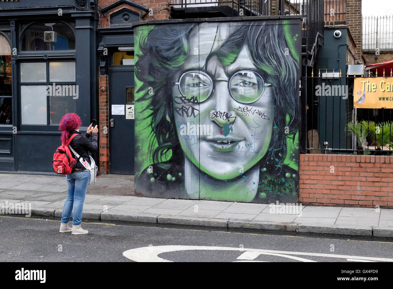 A woman with red hair photographs a portrait of John Lennon. - Stock Image