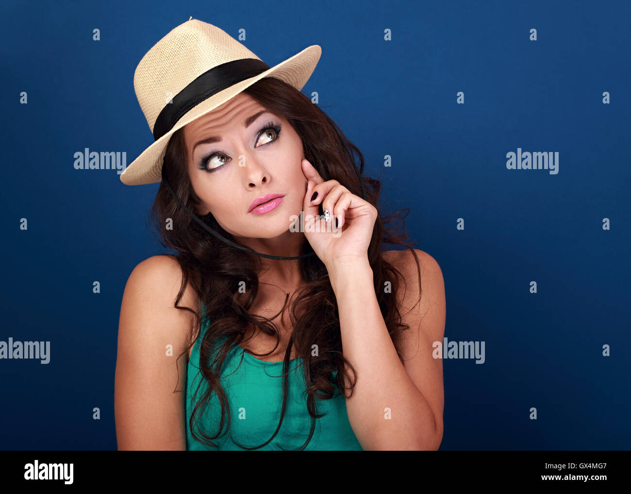 Fun grimacing frightened woman in hat thinking and looking up on empty space background. Curly brown long hair style. - Stock Image