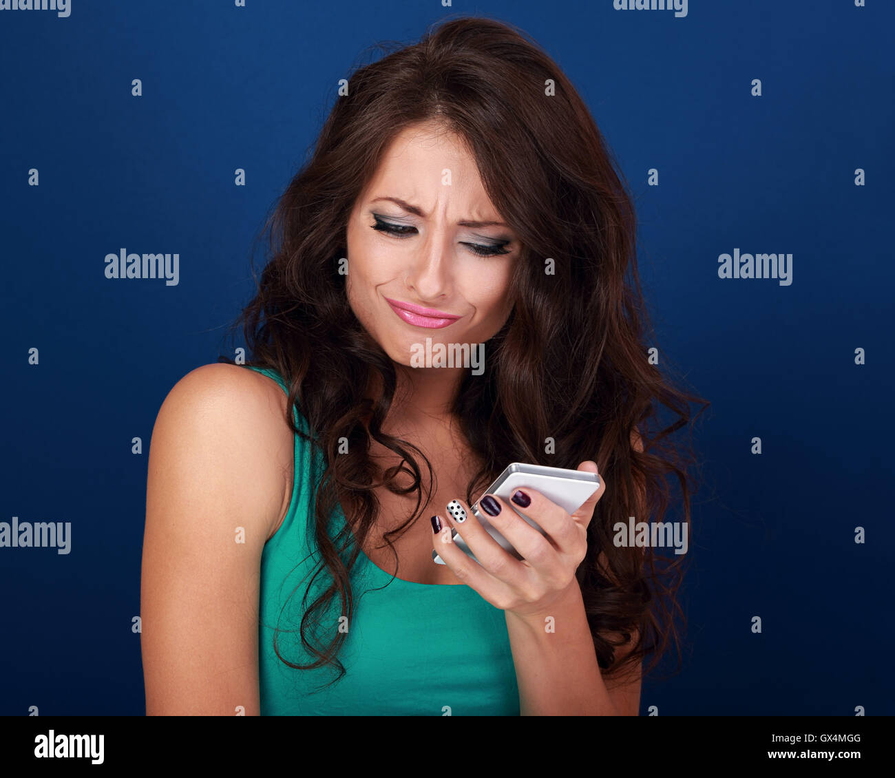 Cranky surprising grimacing young woman reading sms on mobile phone holding it in hand on blue background - Stock Image