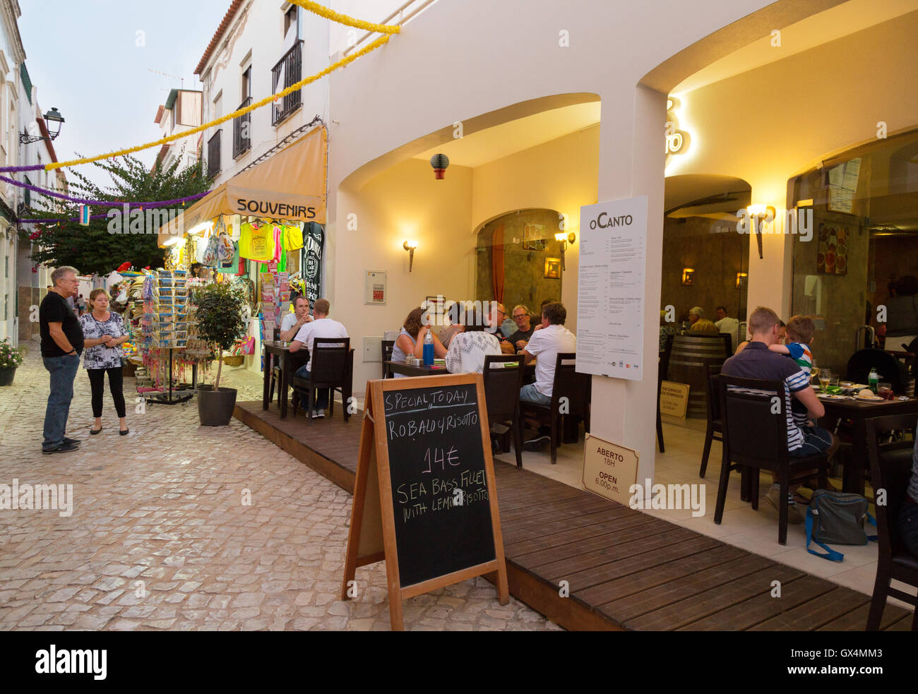 People eating at a restaurant in the evening, Ferragudo, Algarve, Portugal Europe - Stock Image