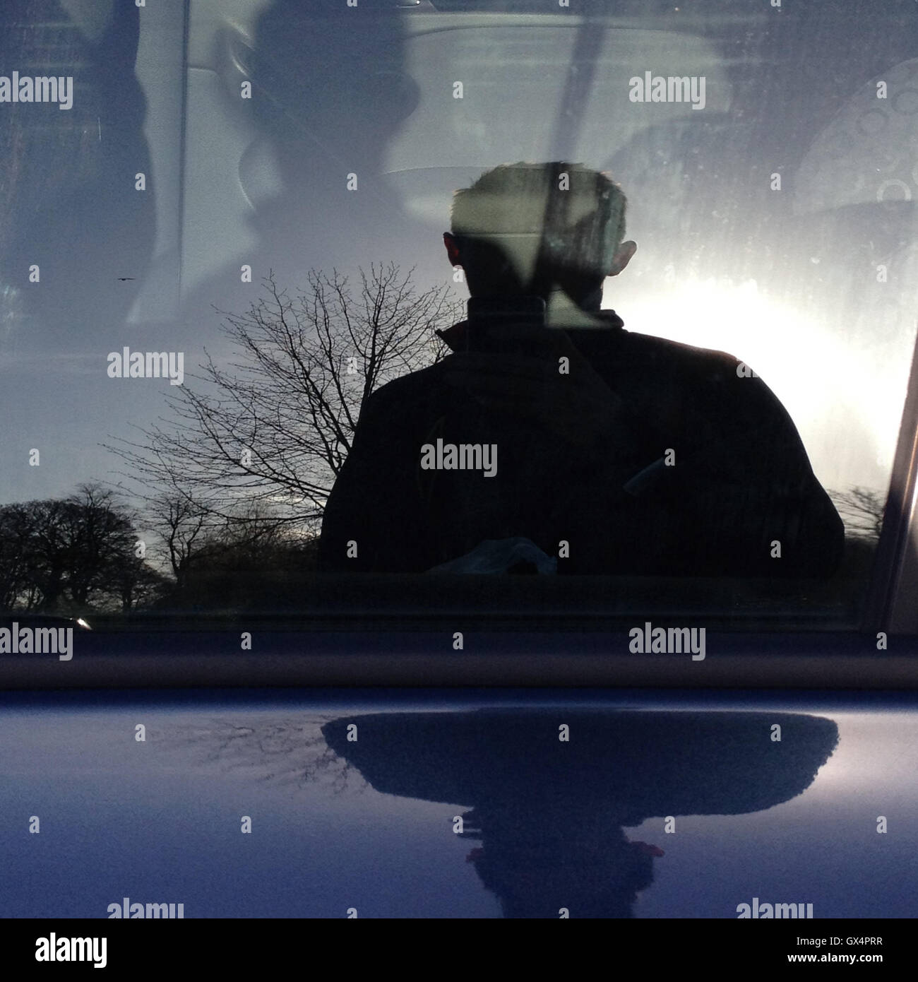 Reflection in side window of car, in Glasgow, Scotland. - Stock Image