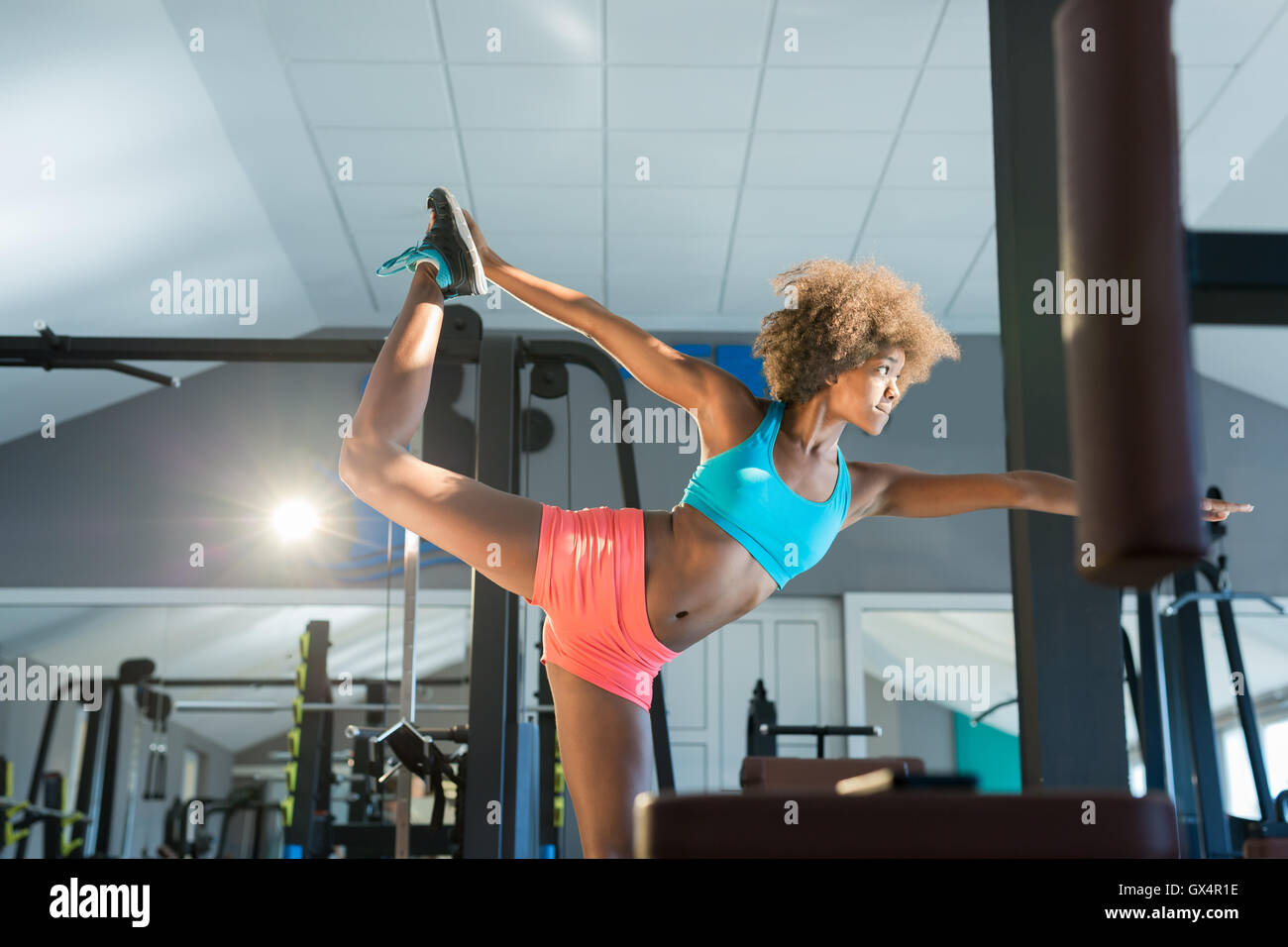 Gym woman stretching her leg for warm-up - Stock Image