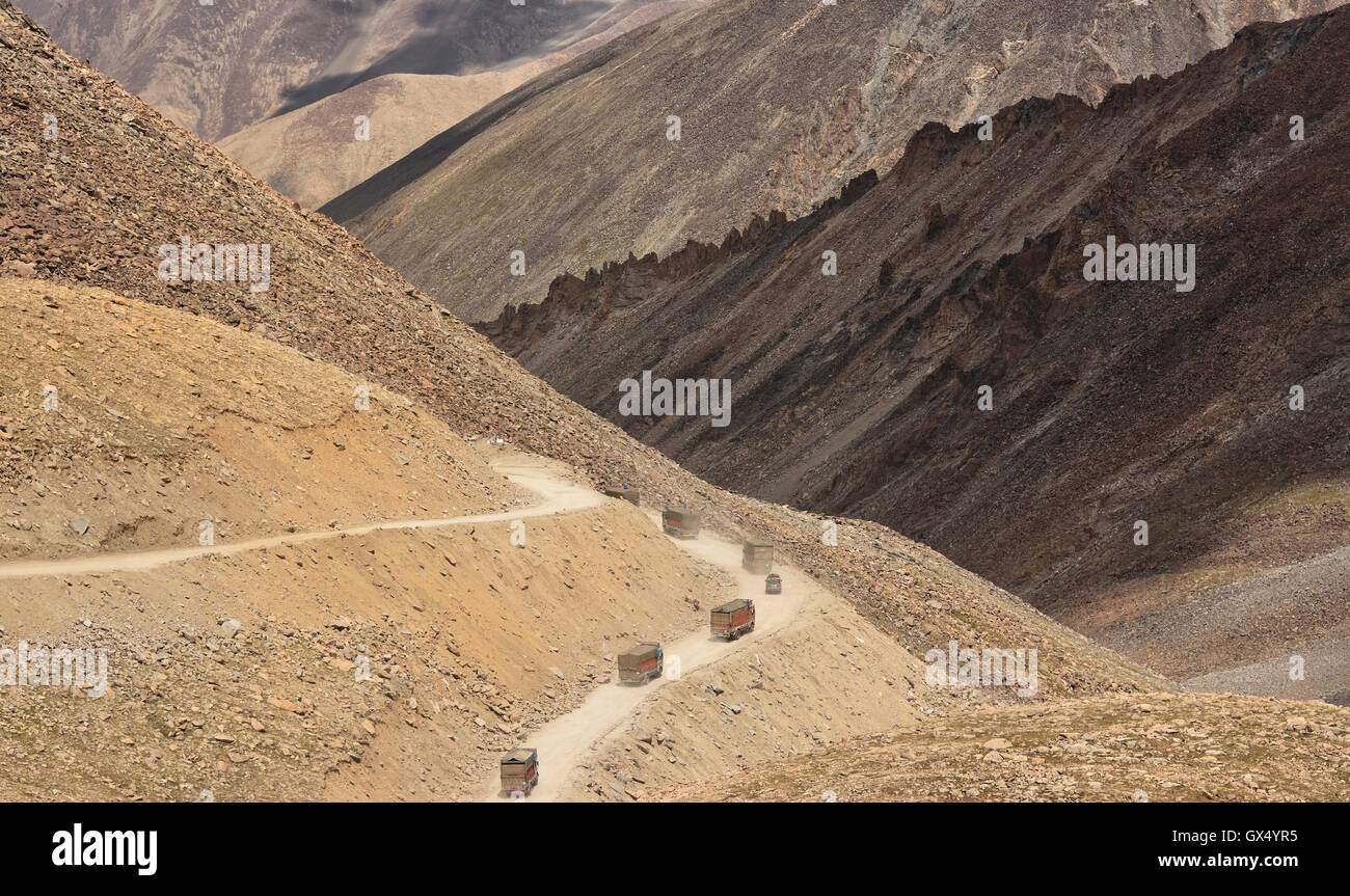 Trucks driving on a mountain road through rocky and barren landscape in Ladakh in the state of Jammu & Kashmir, - Stock Image