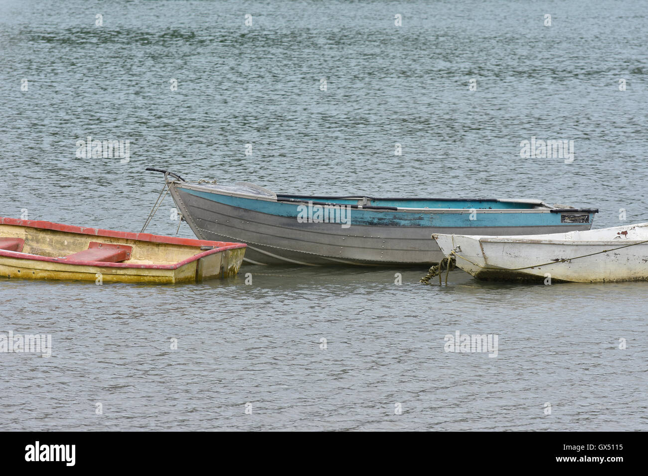 Worn out dinghies on calm water - Stock Image