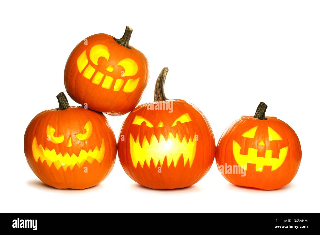 Group of fun lit Halloween Jack o Lanterns isolated on a white background Stock Photo