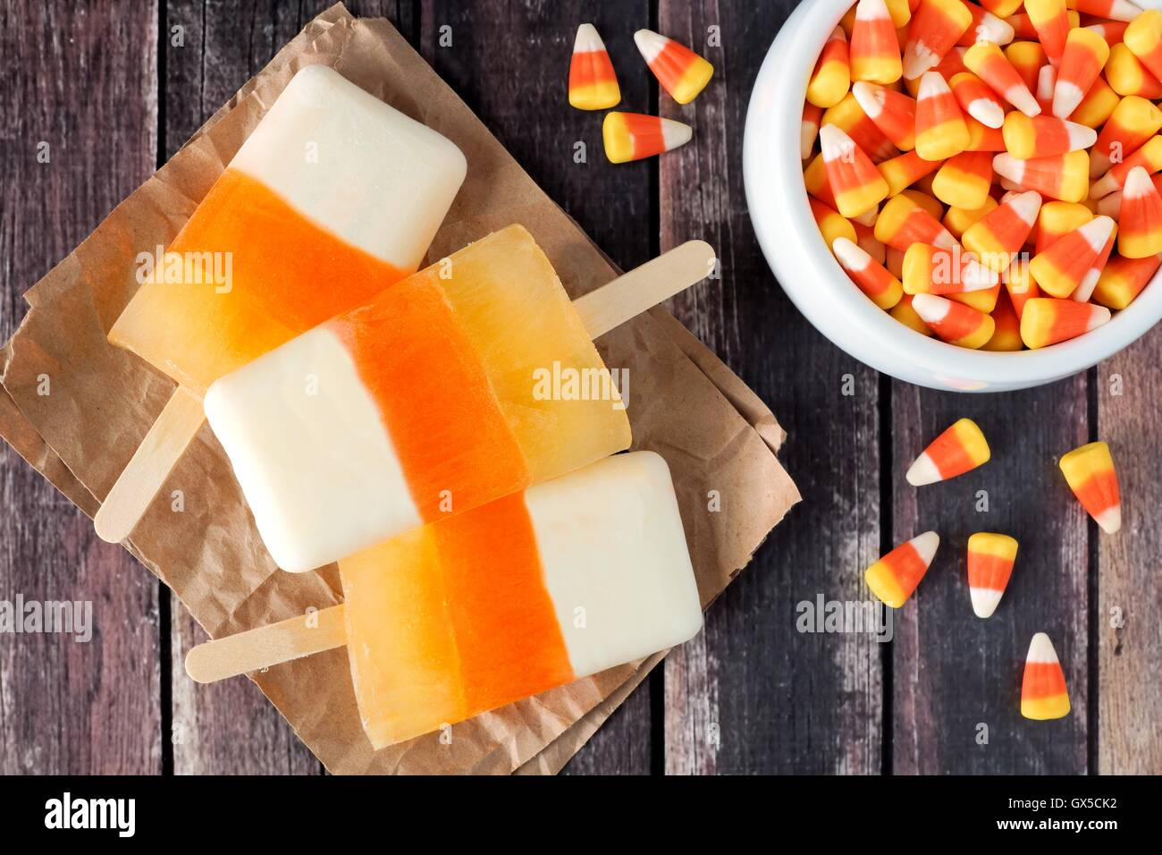 Halloween candy corn popsicles downward view on rustic wood background with bowl of candy - Stock Image