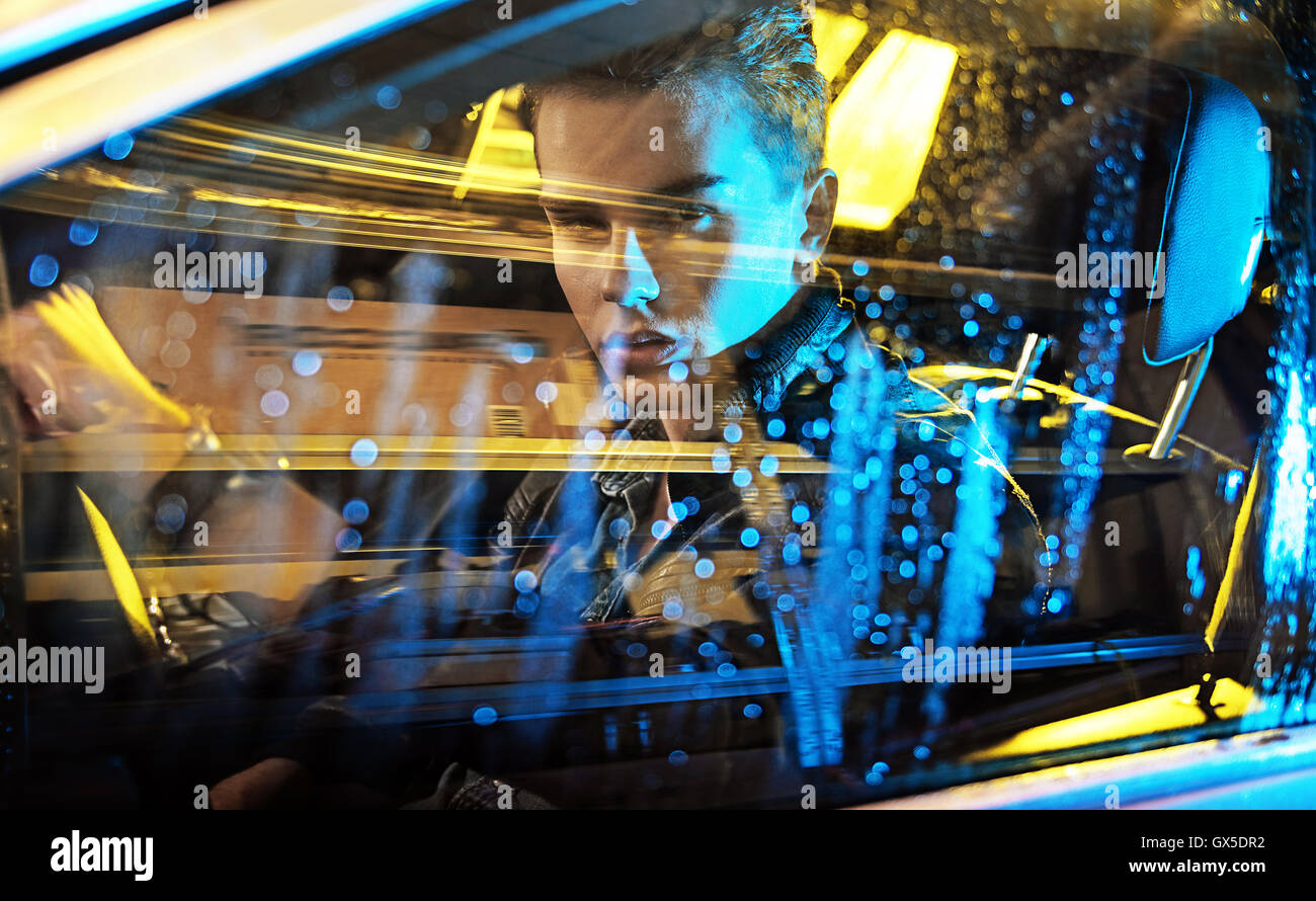 Conceptual picture of a young guy sitting in the car - Stock Image