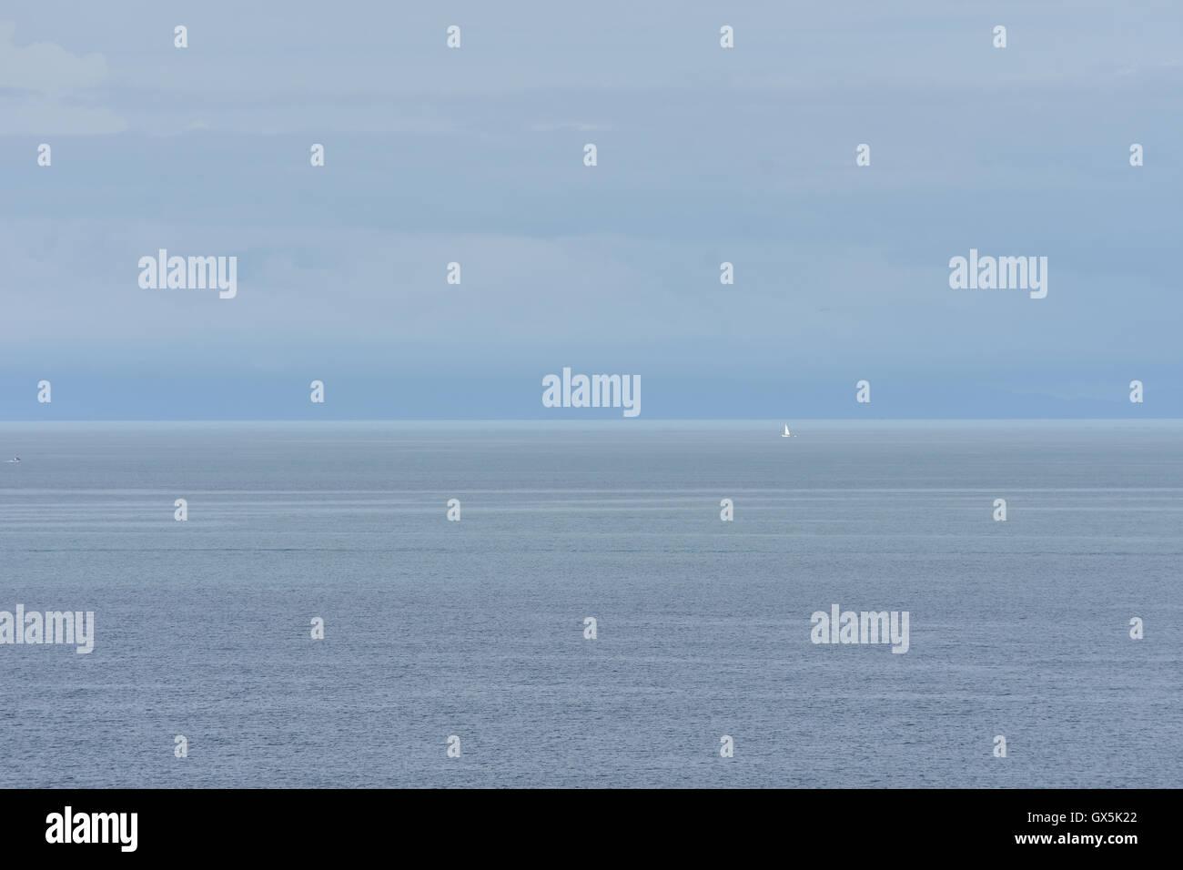 Miniscule sailship on the horizon - Stock Image