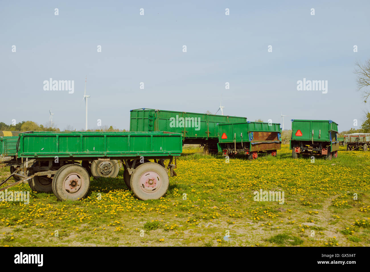Green agricultural trailers on the farm in the morning. - Stock Image